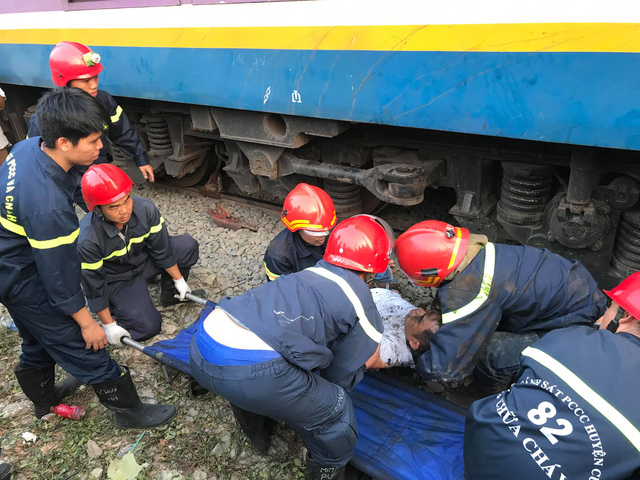 Rescue workers place on a stretcher a man saved from being stuck under a train in Ho Chi Minh City, Vietnam, March 18, 2019. Photo: Xuan Doan / Tuoi Tre