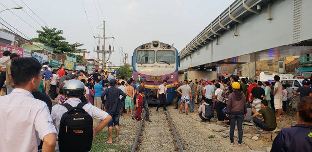 People gather at the train under which a man was stuck in Ho Chi Minh City, Vietnam, March 18, 2019. Photo: Tu Sang / Tuoi Tre