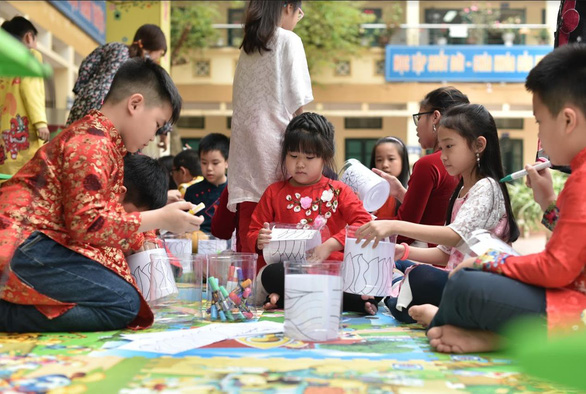 Students at an elementary school in Hanoi paint cookie containers to help create the Rainbow Connection for display at the Singapore Festival.