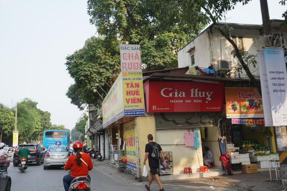 A pedestrian walks on the roadway on Hai Ba Trung Street.