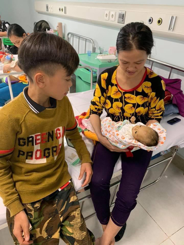 Vi Quyet Chien looks at his younger brother being held by their mother at Vietnam National Children's Hospital in Hanoi, on March 26, 2019 in this photo posted on the Facebook of a doctor.