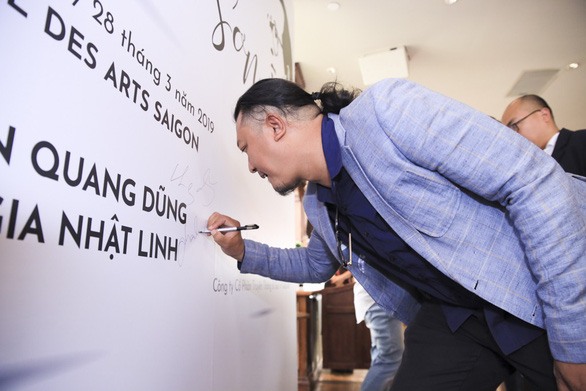 Director Phan Gia Nhat Linh signs on a backdrop at the press conference in Ho Chi Minh City on March 28, 2019. Photo: Organizer