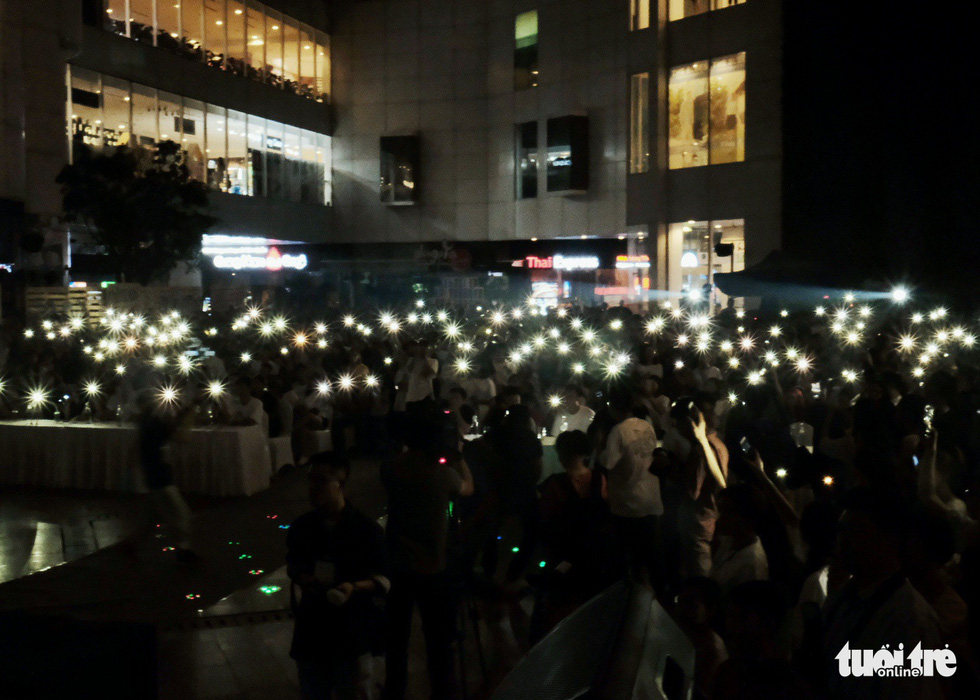 Participants turn on the flash lights of their mobile phones during the event. Photo: Mai Thuong / Tuoi Tre