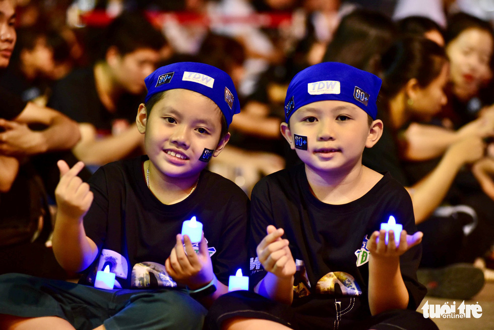 Two young boys take part in the Earth Hour campaign in Ho Chi Minh City. Photo: Duyen Phan / Tuoi Tre