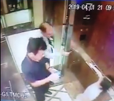 A security guard helps the girl pick her floor, while Linh is using his phone insdie the elevator. Photo: Facebook