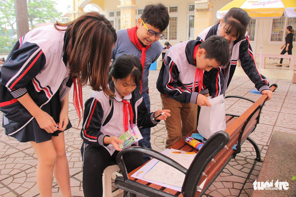 Students gather to praise a schoolmate's piece of art. Photo: Ha Thanh / Tuoi Tre