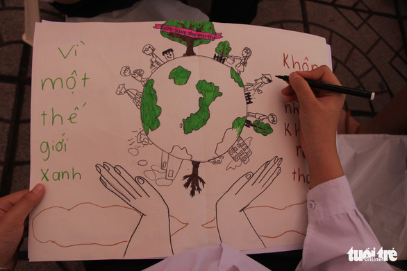 A drawing by a fifth-grader of two hands holding the green earth. Photo: Ha Thanh / Tuoi Tre