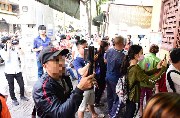 A man goes live on social network while everybody prays at the funeral of comedian Anh Vu in Ho Chi Minh City on April 10, 2019. Photo: Duyen Phan/ Tuoi Tre