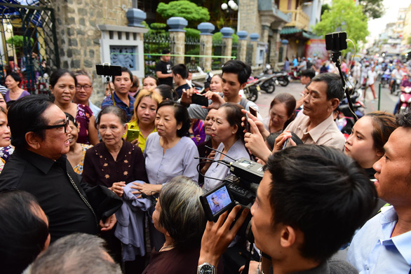People take photos of celebrities during their interview at the funeral of comedian Anh Vu in Ho Chi Minh City on April 10, 2019. Photo: Duyen Phan/ Tuoi Tre