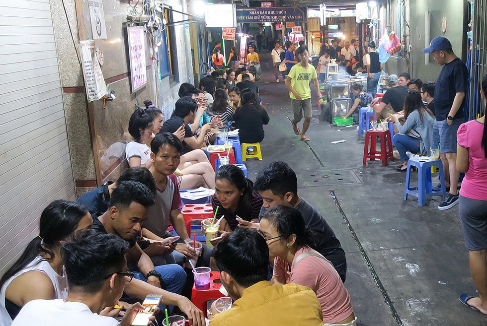 Young people enjoy street food in an alley on Bui Vien Street.