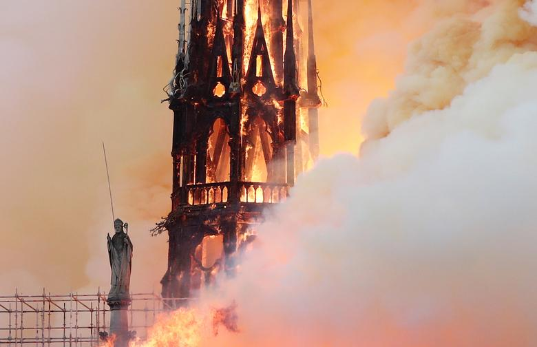 Smoke billows as fire engulfs the spire of Notre-Dame Cathedral in Paris, April 15. REUTERS/Benoit Tessier