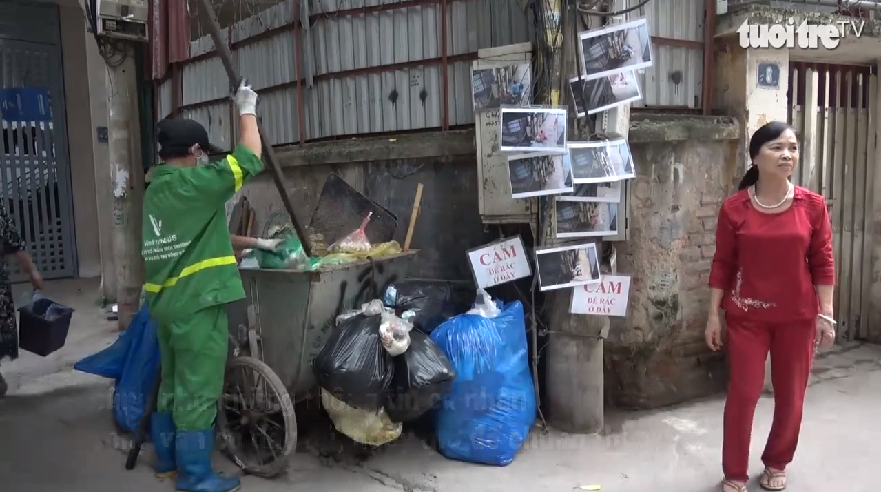 Photos of illegal garbage dumpers are posted on a power pole on a Hanoi alley to discourage violators in this still photo taken from a Tuoi Tre (Youth) newspaper video report.