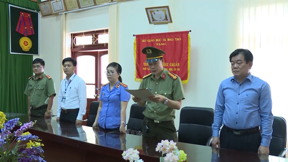 Police officers announce the arrest and prosecution of an education official in Son La Province in northern Vietnam in this still photo taken from a police video.