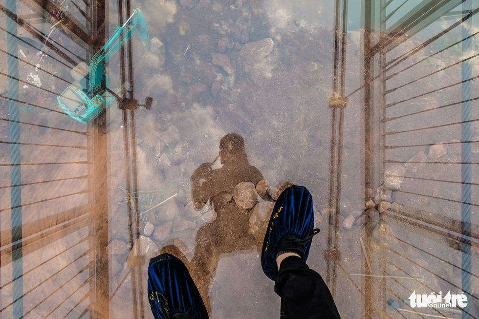 A man steps on  the glass roadway of the Moc Chau 5D-effect bridge. Photo: Nam Tran / Tuoi Tre