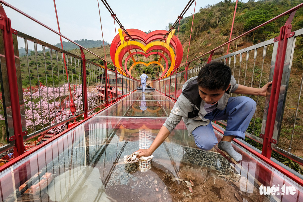 A worker cleans the surface of the glass roadway of the Moc Chau 5D-effect bridge. Photo: Nam Tran / Tuoi Tre