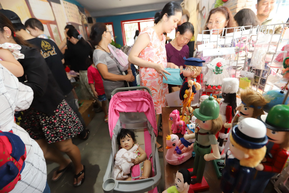 A little girl is carried in a baby stroller to the Doll Flea Market in Ho Chi Minh City. Photo: Tuoi Tre