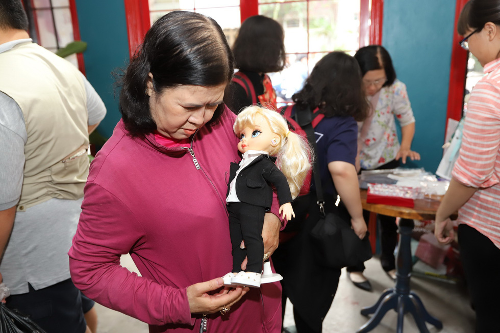 A woman views a doll displayed at the Doll Flea Market in Ho Chi Minh City. Photo: Tuoi Tre