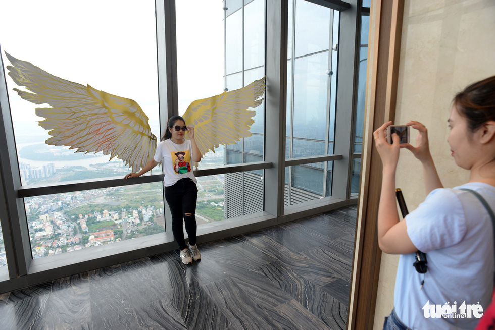A visitor takes a photo with a pair of wings at the observatory deck.