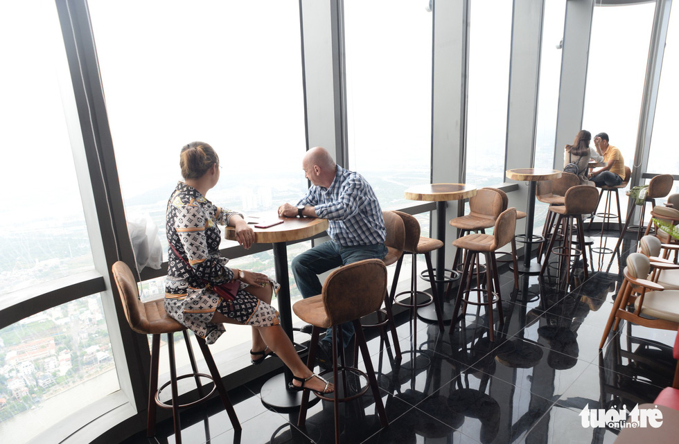 People enjoy their view at a café lounge within the 79th floor.