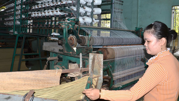 A female worker operates an automatic mat-weaving machine. Photo: H. Phuong / Tuoi Tre
