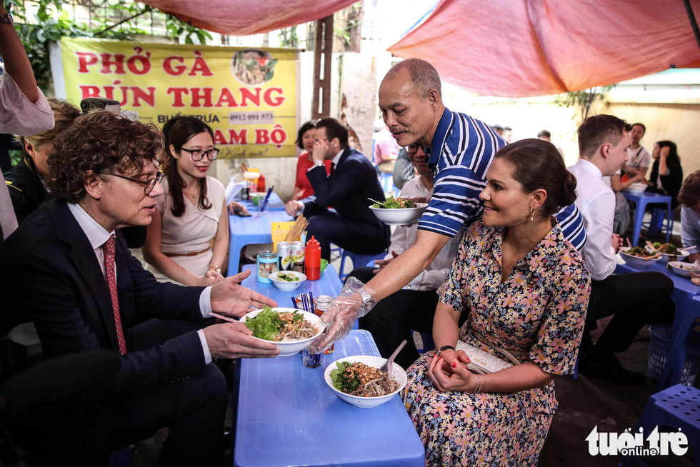 The shop owner hands a bowl of 'bun bo' to Swedish Ambassador to Vietnam Pereric Högberg.