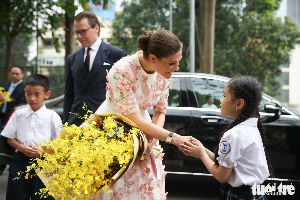 The crown princess greets a young girl during her visit to a local elementary school.
