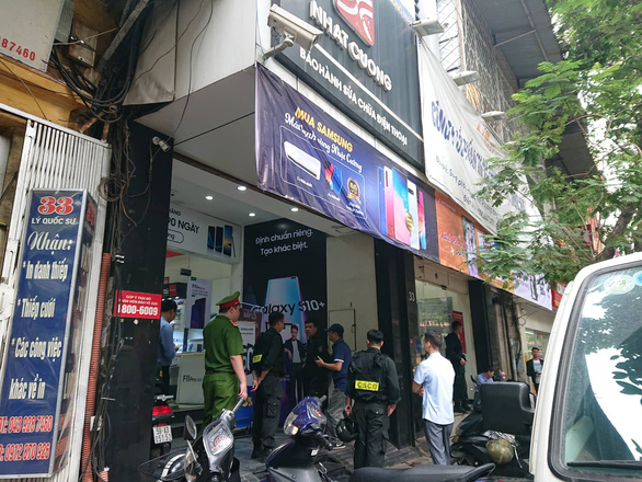 Officers examine an outlet on Ly Quoc Su Street.