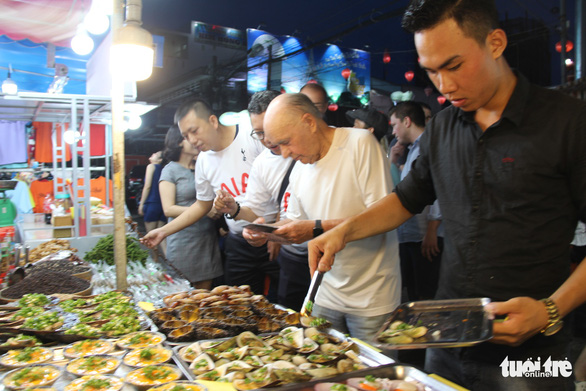 Joe Lewis picks seafood at the night market on Phu Quoc Island, southern Vietnam, on May 10, 2019. Photo: Duy Khanh / Tuoi Tre