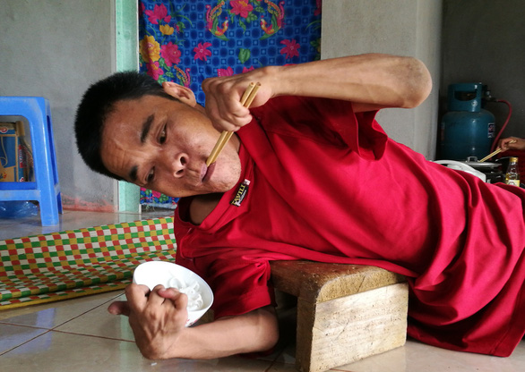 Hoang Than holds a bowl of rice while laying on his side. Photo: Vu Tuan / Tuoi Tre