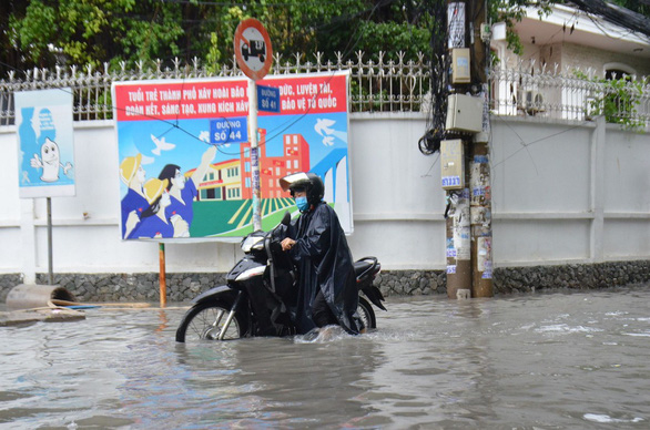 A resident struggles to travel on inundated Road No.41 in Thao Dien Ward, District 2. Photo: Minh Hoa / Tuoi Tre