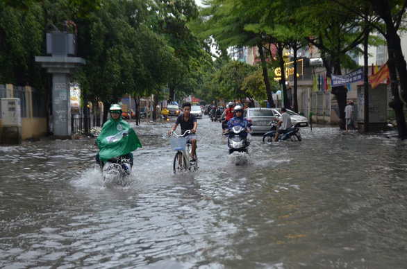 Commuters travel on a flooded street. Photo: Minh Hoa / Tuoi Tre