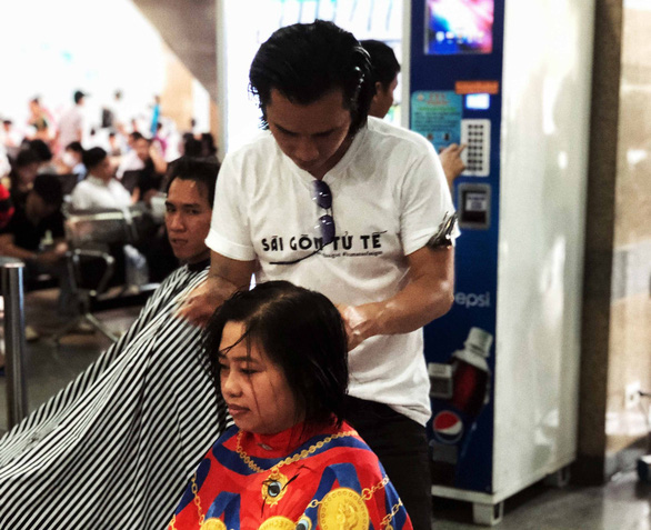 "Vietnamese hairstylist Le Tuan gives poor people free haircuts to promote ""A Beautiful Saigon"" project. Photo: Le Van / Tuoi Tre"