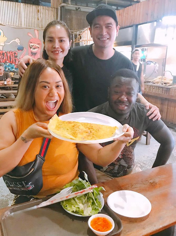 Pham Thanh Danh poses for a photo with foreign tourists who have Vietnamese pancake (banh xeo) at his diner in Ho Chi Minh City. Photo: Quoc Linh / Tuoi Tre