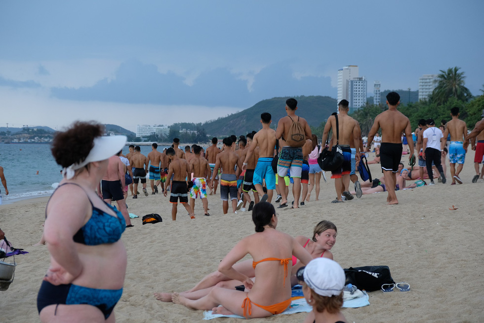 Visitors feast their eyes on the bodybuilders' nice shapes. Photo: Dinh Cuong / Tuoi Tre