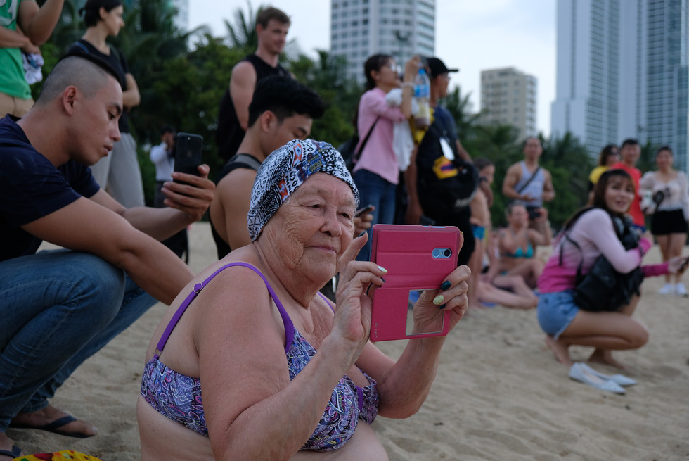 A female tourist takes photos of the bodybuilding contestants. Photo: Dinh Cuong / Tuoi Tre
