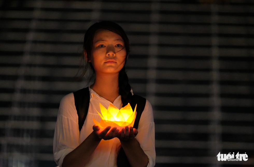 A Buddhism follower holds water lanterns during a mass prayer at the Tam Chuc Pagoda Ha Nam, northern Vietnam, on May 13, 2019. Photo: Nam Tran / Tuoi Tre