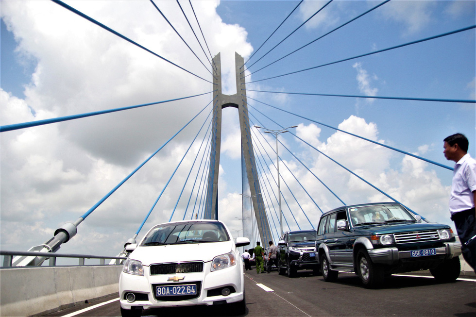 Automobiles of local officials are parked along the bridge.