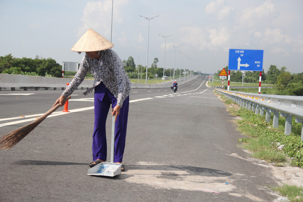 A woman is in charge of cleaning the road which leads to the bridge.