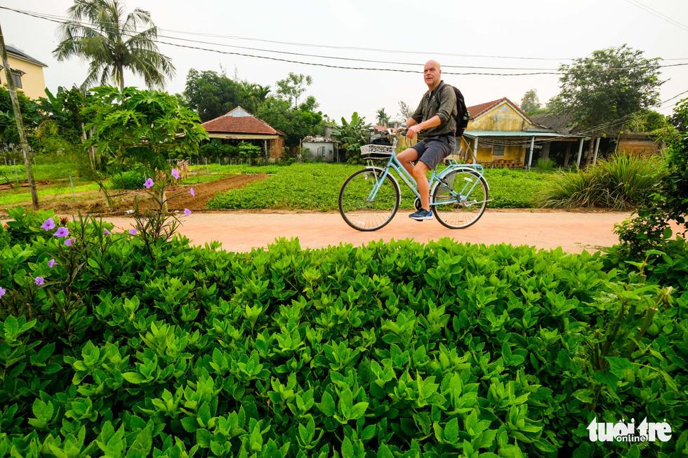 A foreign tourist visits Tra Que vegetable village in Hoi An, Quang Nam, central Vietnam, on a bike. Photo: Mai Vinh / Tuoi Tre