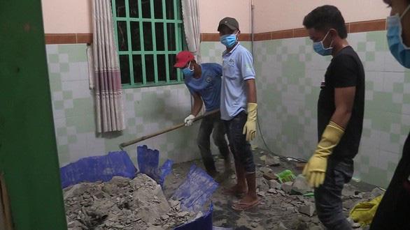 People break the concrete-filled barrel to retrieve the body. Photo: Ba Son / Tuoi Tre
