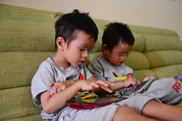 Two children glued to tablet screens. Photo: Quang Dinh / Tuoi Tre
