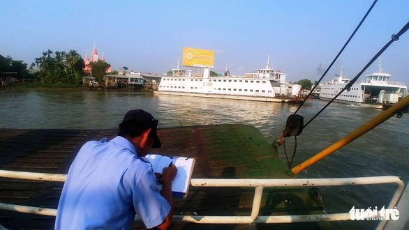 A worker writes about the Vam Cong ferry crossing in a diary. Photo: Mau Truong / Tuoi Tre
