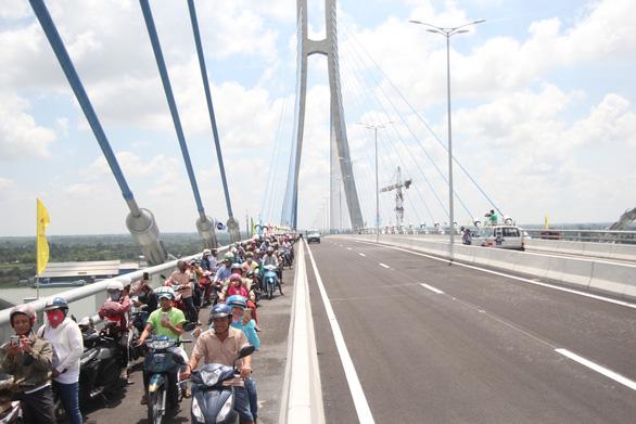 Residents travel on Vam Cong Bridge.