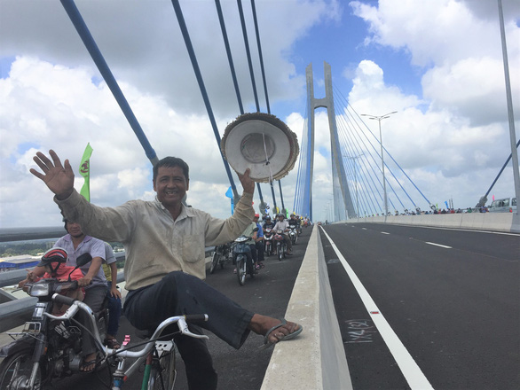 Don, a 66-year-old resident from Dong Thap, rides his bicycle on the bridge.
