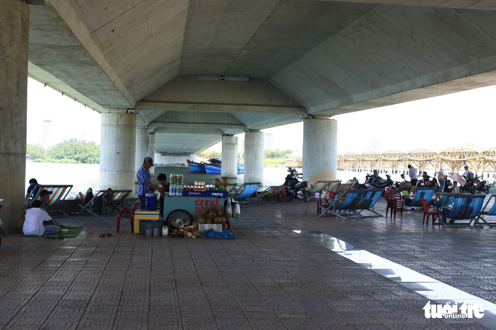 A man sells drinks under a bridge in Da Nang.