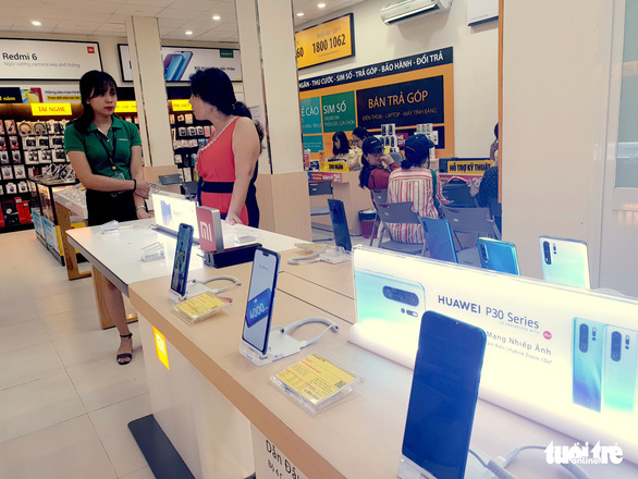 An attendant at a smartphone store in Ho Chi Minh City gives consultation to a customer. Photo: Bong Mai / Tuoi Tre