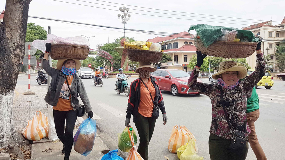 Street vendors carry bamboo panniers of chicken rice along a busy street in Quang Binh, central Vietnam. Photo: Tuoi Tre
