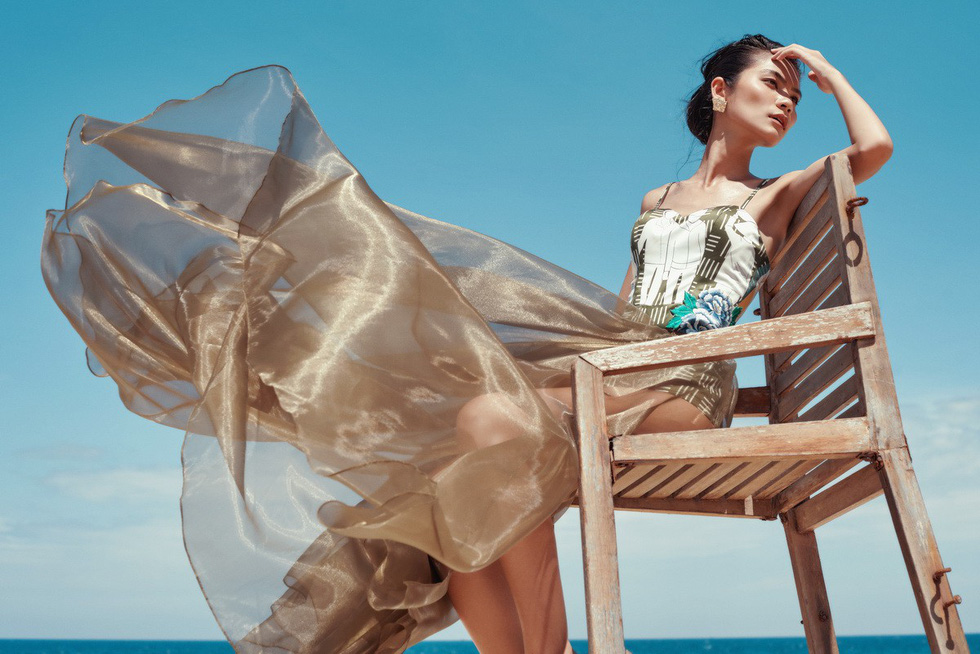 A model showcases a dress featuring a Vietnamese village, part of Ho Tran Da Thao's newest collection -  Dau an duong dai