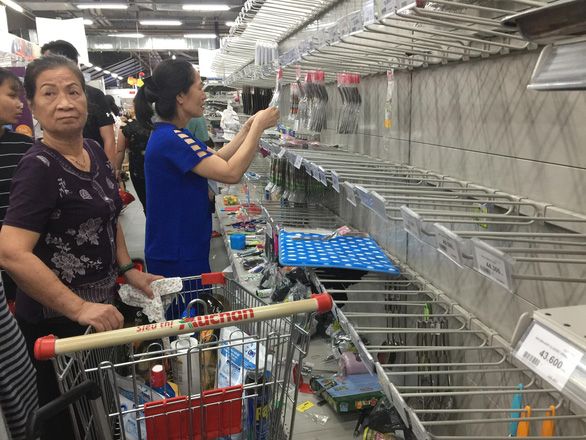 Customers pick up products from sparse shelves at an Auchan supermarket in Ho Chi Minh City on May 21, 2019. Photo: Nguyen Tri / Tuoi Tre