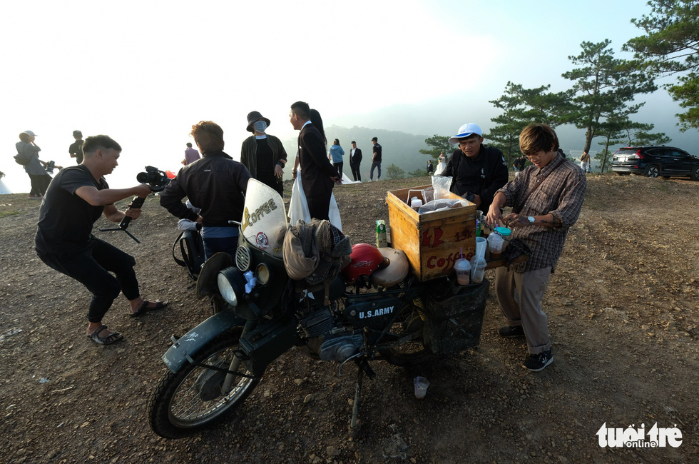 Tran Phi Hung (R) runs a mobile takeaway coffee stand at 'Lovebird Hill' in Lam Dong Province, Vietnam. Photo: Tuoi Tre